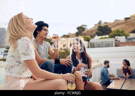 Happy young people having drinks and enjoying while their friends sitting and talking to each other in the background. - Stock Photo