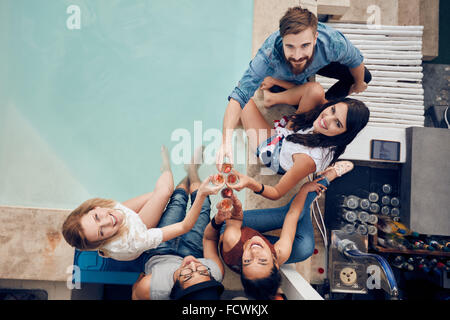 Overhead view of group of friends toasting at party by a swimming pool and looking up at camera smiling. Multiracial - Stock Photo