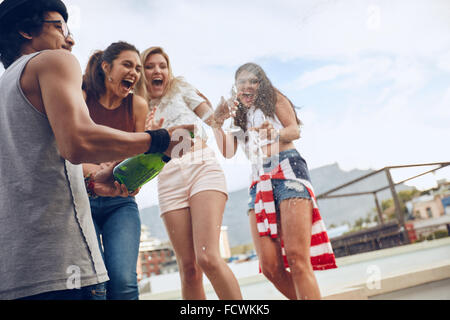 Young man opening a bottle of champagne with female friends standing in background laughing and having fun. Young - Stock Photo