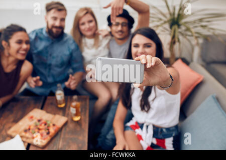 Young friends in a party taking self portrait with smart phone. Focus on mobile phone in woman's hand. Group of - Stock Photo