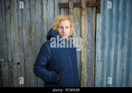 Woman is winter clothes leans against a a rustic shed - Stock Photo