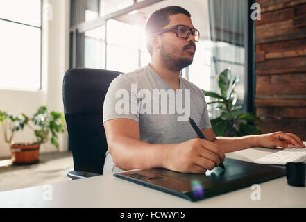 Portrait of young male photo editor at work in his office. Male graphic designer working at his desk using digital - Stock Photo