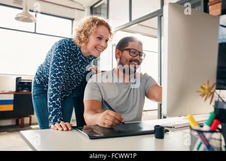 Two young male and female designers working together, with man editing artwork using graphics tablet and a stylus. - Stock Photo