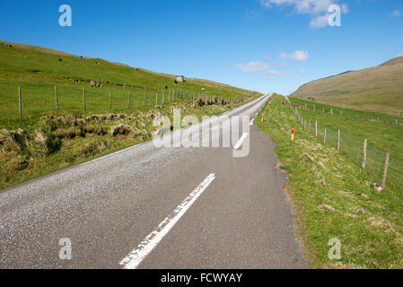 Typical street and landscape on the Faroe Islands as seen from Sandur with blue sky, green grass, mountains and - Stock Photo