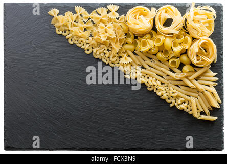 Variety of types and shapes of Italian pasta on a dark stone background. - Stock Photo