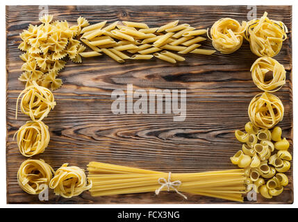 Variety of types and shapes of Italian pasta on wooden background. - Stock Photo