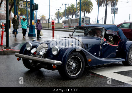 Classic car driving in San Francisco on a rainy day - Stock Photo