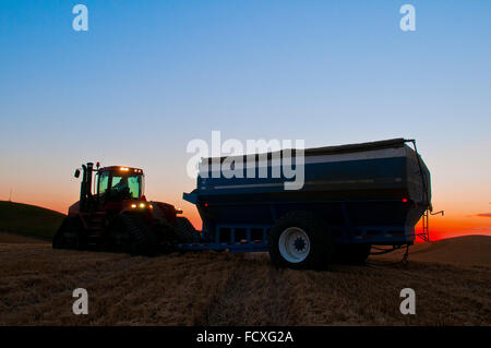 A tractor pulling  a grain cart in a wheat field at sunset during harvest in the Palouse region of Washington - Stock Photo