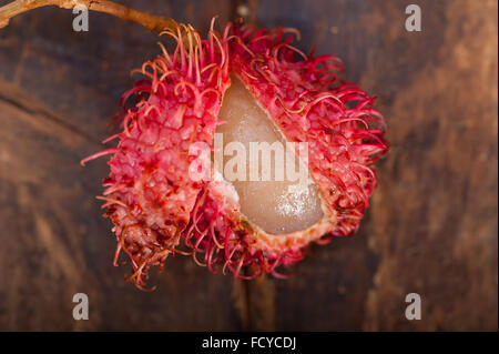 fresh tropical rambutan fruits over rustic wood table - Stock Photo