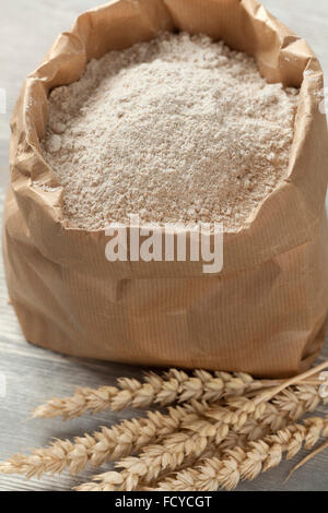 Dried wheat and wheat flour in a paper bag - Stock Photo