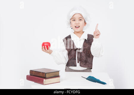 Boy in a classical scholar style holding an apple with pointing finger at desk with old books and a feather pen - Stock Photo