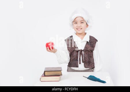 Boy in a classical scholar style holding an apple at desk with old books and a feather pen - Stock Photo