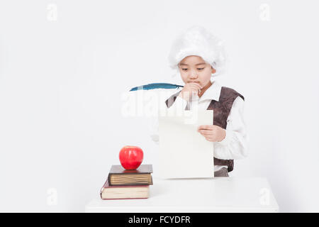 Boy in a classical scholar style holding a piece of paper and a feather pen at desk with an apple on old books - Stock Photo