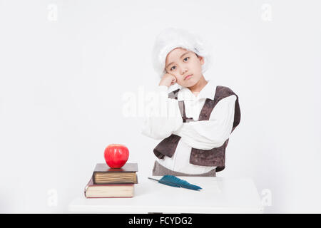 Boy in classical scholar style thinking at desk with an apple on old books and a feather pen on the desk - Stock Photo