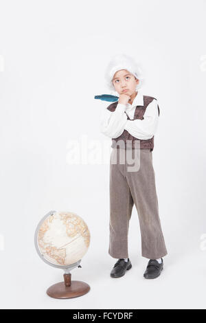 Boy in classical scholar style holding a feather pen and standing behind a globe with the gesture of thinking - Stock Photo