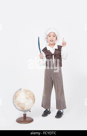 Boy in classical scholar style standing behind a globe with a feather pen and with his finger pointing up - Stock Photo