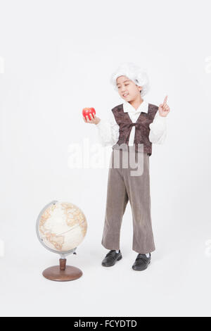 Boy in classical scholar style holding an apple with his finger up and standing behind a globe looking down - Stock Photo