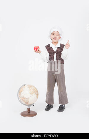 Boy in classical scholar style holding an apple with his finger up and standing behind a globe staring forward with - Stock Photo