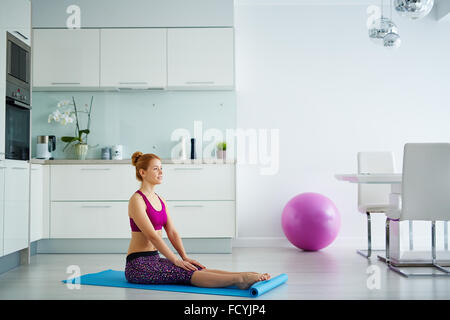 Young woman sitting on mat with stretched legs - Stock Photo