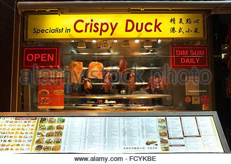 Chinese restaurant in Soho, with crispy duck displayed in window, menu outside below window. London, UK. - Stock Photo
