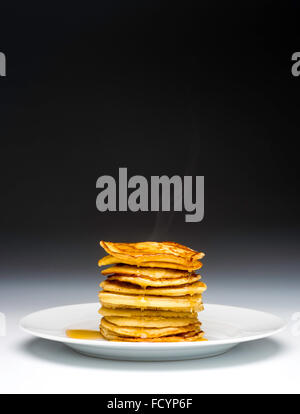 Stack of pancakes on white plate drizzled with syrup - Stock Photo