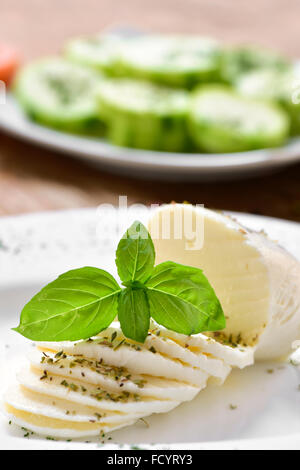 closeup of a plate with a sliced fresh cheese on a table, and a plate with chopped courgette in the background - Stock Photo