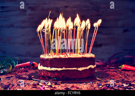 a cake topped with some lit candles before blowing out the cake, on a rustic wooden table full of confetti, party - Stock Photo