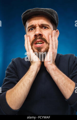 The portrait of a young man in a cap currently experiencing feelings of grief and horror on a blue background - Stock Photo