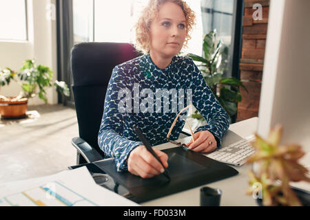 Young female editor using graphics tablet to do work at her desk in the office. Professional graphic designer at - Stock Photo