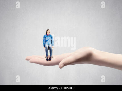 Young woman sitting in chair on female palm - Stock Photo