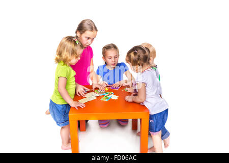 Happy kids playing with puzzles isolated on white. Team work, creativity concept. - Stock Photo