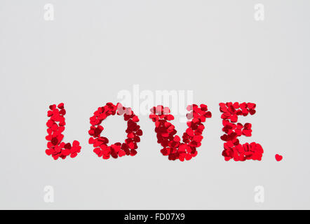 The word LOVE spelled out in small heart shapes and decorations on a white, isolated background. - Stock Photo