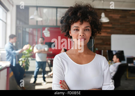 Portrait of woman standing in busy creative office looking at camera. Attractive female creative professional in - Stock Photo