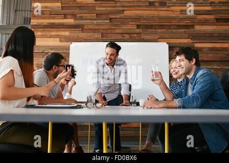 Group of happy young people having a business meeting. Creative people sitting at table in boardroom with man explaining - Stock Photo