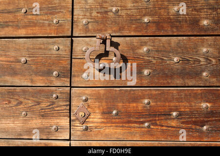 Old metal doorknocker on the wooden gate fixed with rivets in Bergamo, Lombardy, Italy. - Stock Photo