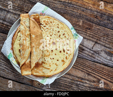 Closeup of thin fine pancakes on a wooden board - Stock Photo