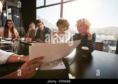 Closeup of hands of young man explaining business plan to colleagues. Creative people meeting in conference room. - Stock Photo