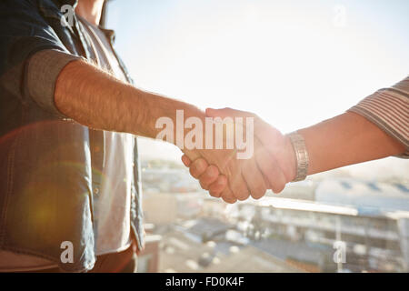 Closeup of two shaking male hands with sun flare. Focus on handshake against cityscape. - Stock Photo
