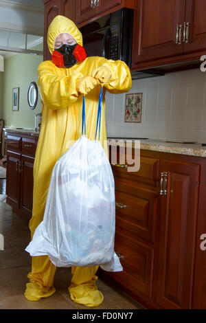 Woman dressed in yellow haz mat outfit with ventilator taking out the garbage in kitchen. - Stock Photo