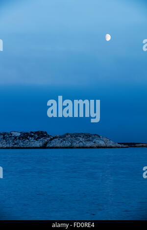 Canada, Nunavut Territory, Rankin Inlet, Moon sets above Marble Island on summer evening along western shore of - Stock Photo