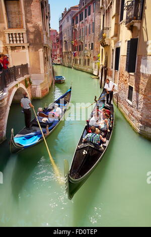 Venice - Gondola with tourists on the canal, Italy - Stock Photo