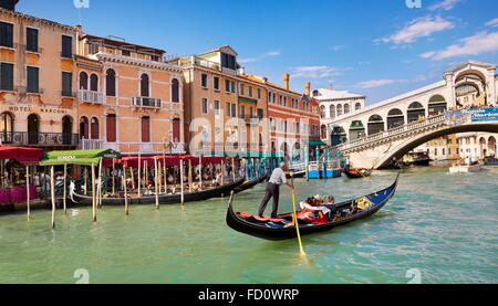 Venice - Grand Canal, tourists in gondola exploring Venice, Italy - Stock Photo