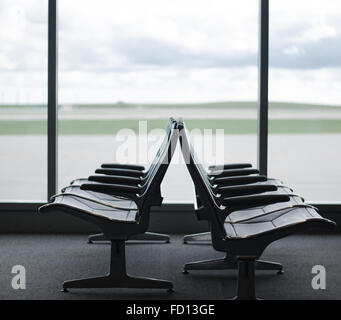 Empty chairs in an airport departure lobby - Stock Photo