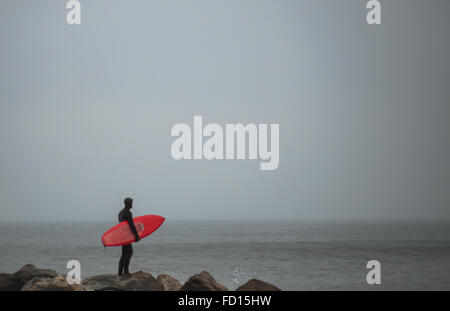 Surfer with red surfboard standing on the rock jetti. Photographed in Rockaway Beach, Queens, NY on December 29, - Stock Photo