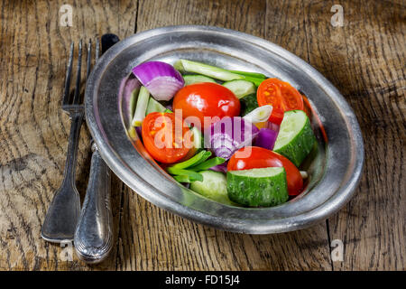 Fresh vegetables in a silver flatware on old wooden table. Selective focus - Stock Photo