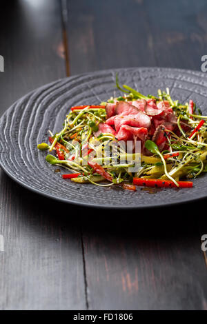 Authentic salad with bacon fresh red pepper, sprouts, sesame and olive oil on a black plate. Morning atmospheric - Stock Photo