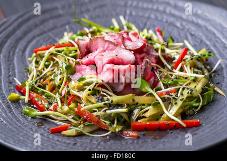 Authentic salad with bacon fresh red pepper, sprouts, sesame and olive oil on a black plate. Morning atmospheric lighting,