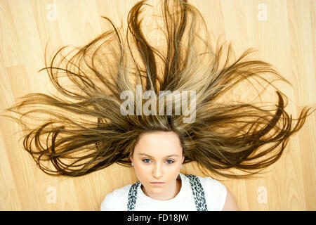 Head and shoulders, blonde teenage blue eyed girl laying on floor looking directly at viewer. Hair sprayed out wildly - Stock Photo