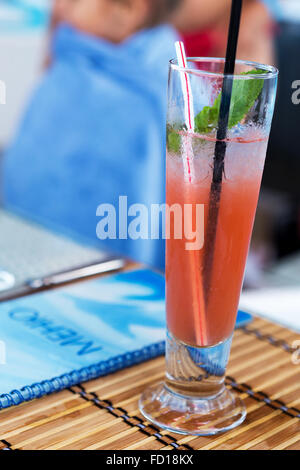 Light alcoholic drink with watermelon juice and ice in the glass. Blur beautiful bouquet of flowers. Soft selective - Stock Photo