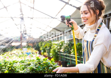 Happy pretty woman gardener in uniform watering plants with garden hose in greenhouse - Stock Photo